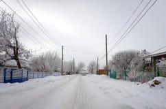 与领域和冷淡的树的美好的农村风景在降雪下 免版税库存照片