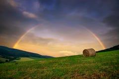 与领域和大包的彩虹农村风景干草 在斯洛伐克村庄夏时的,斯洛伐克附近的典型的小山 库存图片