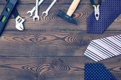 与领带的愉快的父亲` s天概念,礼物和工具倒空在一个木台式视图的笔记本在舱内甲板位置样式 免版税库存图片