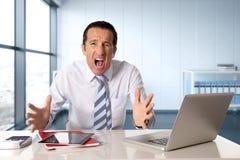 与领带的被注重的资深商人在研究计算机膝上型计算机的危机在重音的书桌在压力下 库存照片