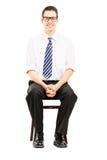 与领带的年轻男性坐一个木椅子等待的工作  免版税库存照片