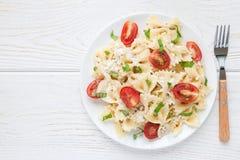 与领带面团、希腊白软干酪、西红柿、芥末和蓬蒿,顶视图,拷贝空间的意大利面制色拉 免版税库存照片