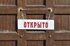 与题字的白色标志用俄语我们关于开放的`在与老金属铆钉的棕色木门-减速火箭的织地不很细背景 免版税库存图片