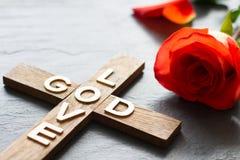 与题字神的复活节基督徒木十字架是爱,并且红色上升了抽象宗教背景 免版税库存照片