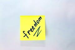 与题字自由的黄色贴纸在蓝色背景 免版税库存照片