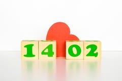 与题字2月14日的木立方体和红色心脏塑造 免版税库存图片