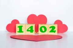 与题字2月14日的木立方体和红色心脏塑造 库存图片