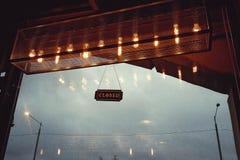 与题字`的一个标志在咖啡馆的美好的内部的晚上关闭了在一个大窗口前面的` 免版税图库摄影