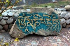 与题字Om玛尼Padme嗡嗡声的被雕刻的石头 库存图片