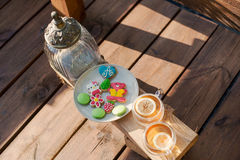 与颜色形象饼干的茶在室外游廊俯视的湖岸 库存照片