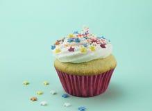 与颜色星的一块香草杯形蛋糕洒反对软的gree 免版税库存照片
