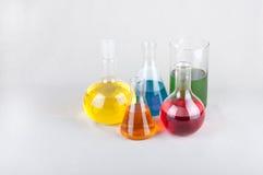 与颜色液体的实验室玻璃器皿在桌上 免版税图库摄影