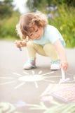 与颜色白垩片断的逗人喜爱的小孩女孩图画  免版税库存图片