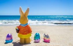 与颜色的复活节兔子在海洋海滩怂恿 库存图片