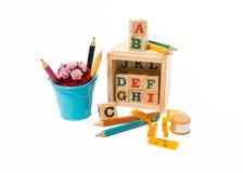 与颜色铅笔、夹子、磁带和蓝色桶的木字母表块花 免版税库存图片