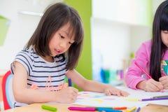 与颜色铅笔的学龄前女孩孩子图画在t的白皮书 免版税库存照片