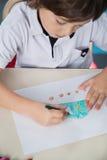 与颜色铅笔的男孩图画在教室 免版税库存图片