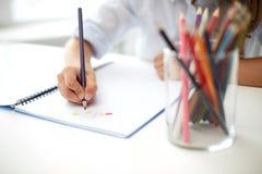与颜色铅笔笔的女孩图画在笔记本 库存照片