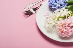 与风信花的春天欢乐表设置在桃红色背景开花 免版税库存照片