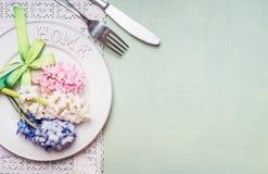 与风信花的欢乐桌餐位餐具开花装饰、板材、叉子和刀子在浅绿色的背景,顶视图 免版税库存照片