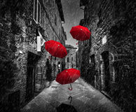 与风和雨的Umrbellas飞行在黑暗的街道上在一个老意大利镇在托斯卡纳,意大利 库存图片