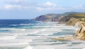 与风大浪急的海面的巴斯克国家海岸线 免版税库存图片