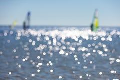 与风帆冲浪者的Defocused海景海表面上 免版税库存图片
