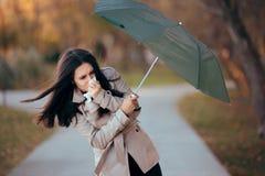 与风战斗的女孩拿着下雨天气的伞 图库摄影