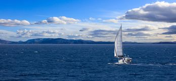 与风的风船旅行在风平浪静帮助, 多云天空背景,横幅 免版税库存照片