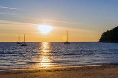 与风船客船和汽船相接的五颜六色的日落在金黄小时和风平浪静的前面 库存照片