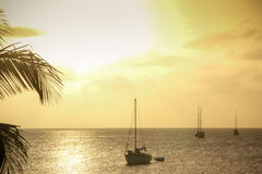 与风船的明亮的黄色日落, Caye填缝隙工伯利兹 库存照片