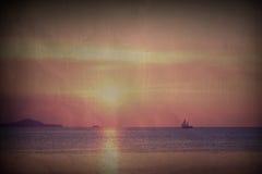 与风船的淡色热带海滩日落在葡萄酒样式 库存图片