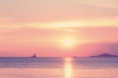 与风船的淡色热带海滩日落 免版税库存照片