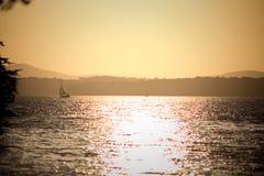 与风船的金黄日落在湖拉尼尔 库存图片