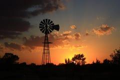 与风车剪影的堪萨斯金黄天空 免版税图库摄影
