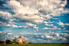 与风车和农场的Cloudscape,种田 绿色领域的,农业磨房和村庄房子 农村风景 免版税图库摄影