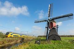 与风车和火车的荷兰风景 免版税库存图片