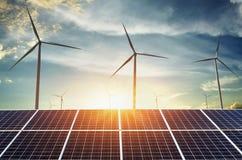 与风轮机和日落的太阳电池板 概念清洁能源 库存图片