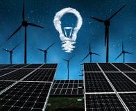 与风轮机和电灯泡的太阳电池板从云彩在夜 免版税库存图片