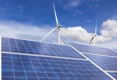 与风轮机的太阳能电池在蓝天背景的杂种能源厂系统驻地 免版税库存照片