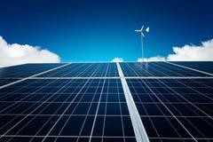 与风轮机的蓝色太阳电池板在蓝天 免版税库存照片