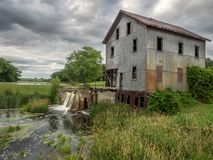 与风雨如磐的天空的老磨房 库存照片