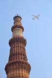 与飞机在天空,德里,印度的Qutub Minar塔 免版税库存图片