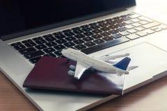 与飞机的旅行护照在预定的票的一台膝上型计算机在网上 库存图片