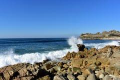 与飞溅反对岩石和史前解决废墟的波浪的狂放的海滩 巴罗纳,加利西亚,西班牙 晴天,蓝天 库存照片