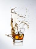与飞溅和冰块的威士忌酒饮料 免版税库存照片
