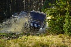 与飞溅的越野车或SUV横穿水坑 召集,竞争和四轮驱动的概念 马达 库存图片