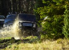 与飞溅的越野车或SUV横穿水坑 在秋天自然背景的越野种族 召集,竞争 库存照片