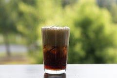 与飞溅CO泡影的冰可乐 喝与冰,特写镜头,发嘶嘶声,嘶嘶响 图库摄影