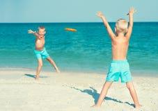 与飞碟的兄弟戏剧在海滩 您系列节日快乐的夏天 免版税图库摄影